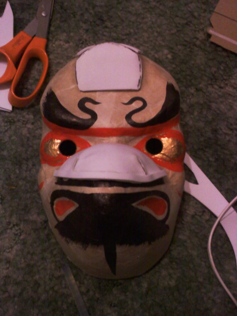 Tengu mask made of paper mache with craft foam accents being added.