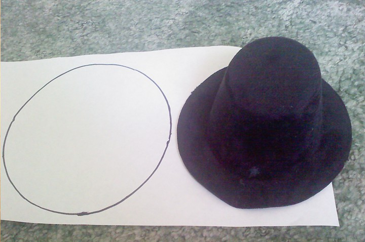 Making a pattern of the hat pieces on wax paper.
